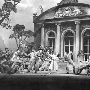 """Димитри Иванов (в средата на сцената) танцува в пиесата """"Гласът на Америка"""" в Народния театър, постановка на Филип Филипов около 1950 г. Пиесата представя военен сюжет с американски войници в Европа. Димитри е поканен като статист да играе американски войник, който танцува степ, заедно с балерината Вера Минчева и с Васил Андреев, станал известен по-късно като автор на песни и мениджър на певеца Емил Димитров. Вдясно, излегналият се на стола е актьорът Георги Георгиев-Гец."""
